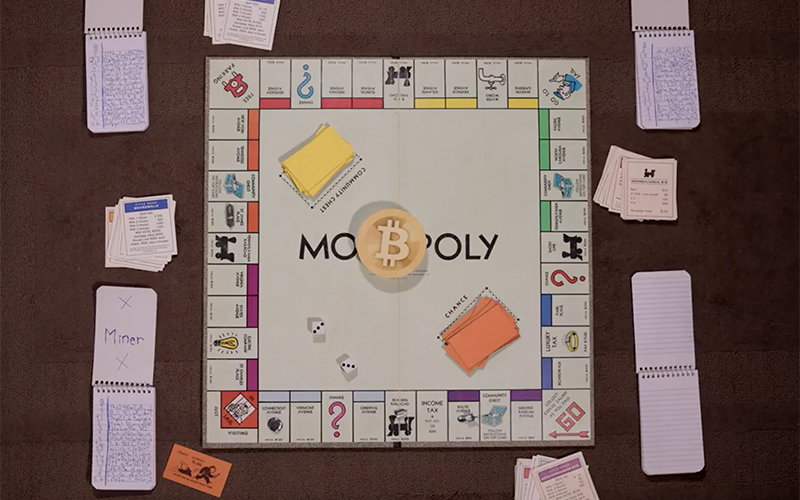 A monopoly board with a bitcoin in the middle of the board.