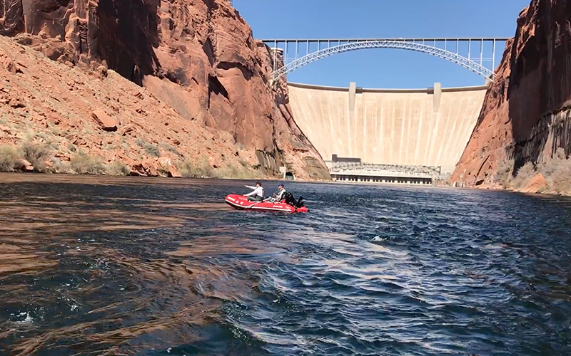 Two people river rafting at Glen Canyon by dam