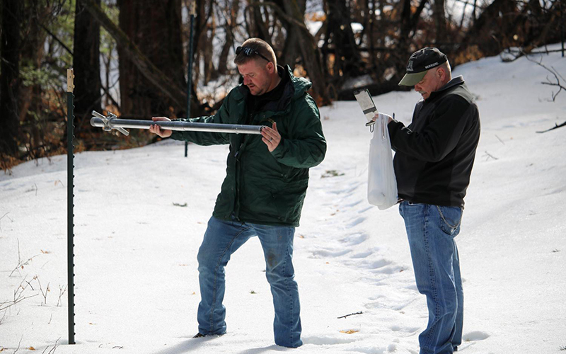 Two surveyors investigate the depth of a snowpack
