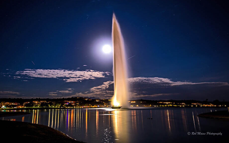 the fountain at Fountain Hills spouts water into the sky at night with the moon illuminating the background