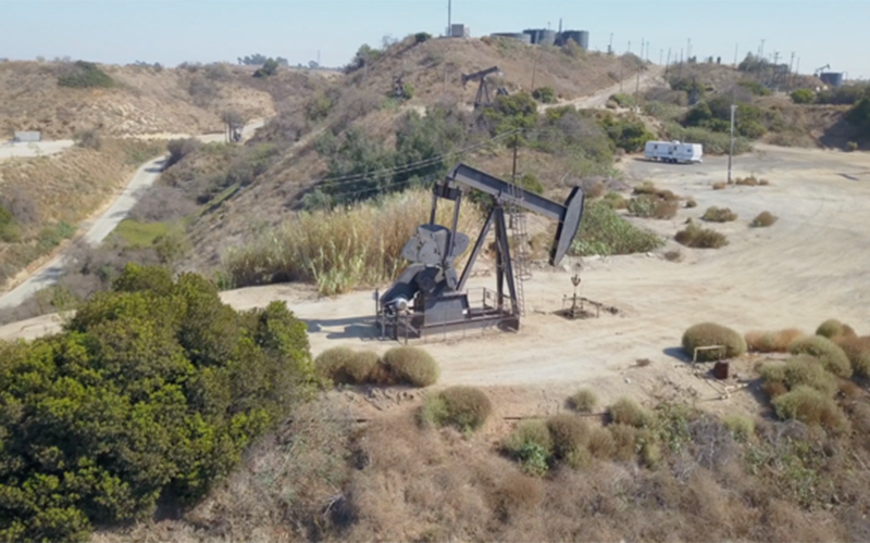 A fracking tower works in a remote desert area