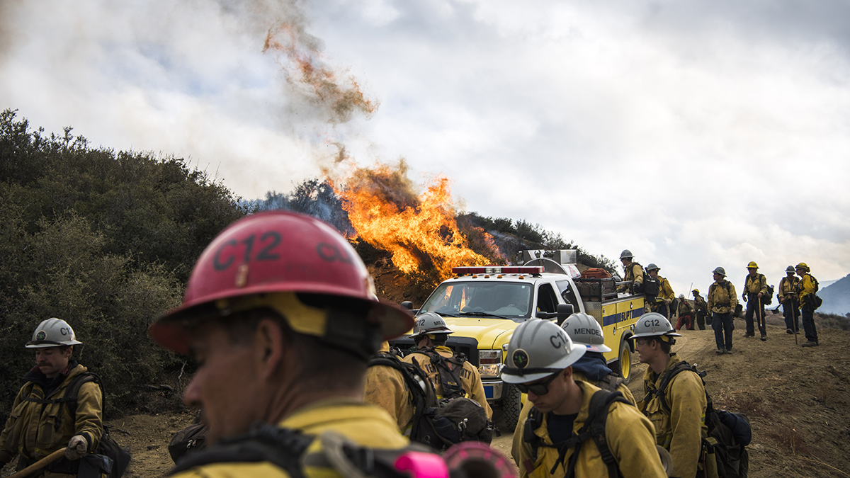 A fire on the mountain surrounded by firemen.