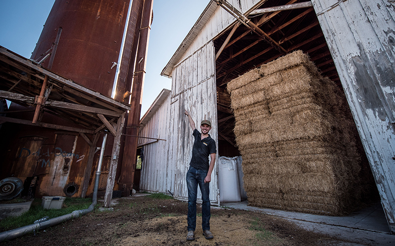 Yann Raymond smiles as he points out the silo that holds unprocessed barley.