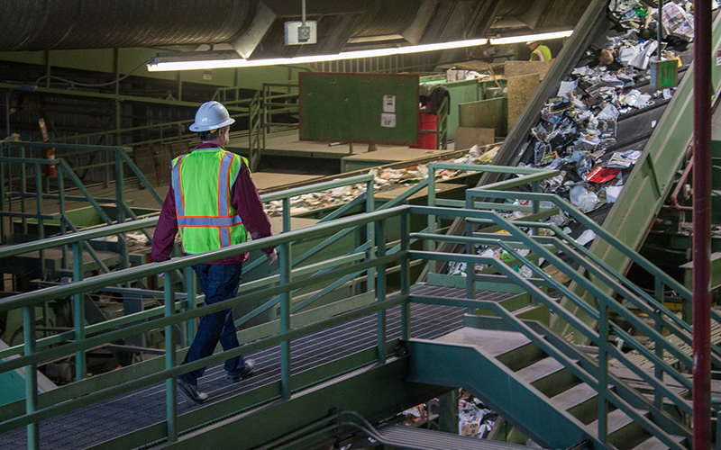 A man walks by moving conveyor belts of materials like paper and plastic.
