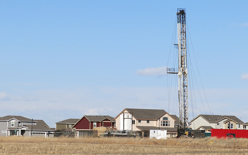 """Oil tower surrounded by suburban homes in rural area with tall grass"""