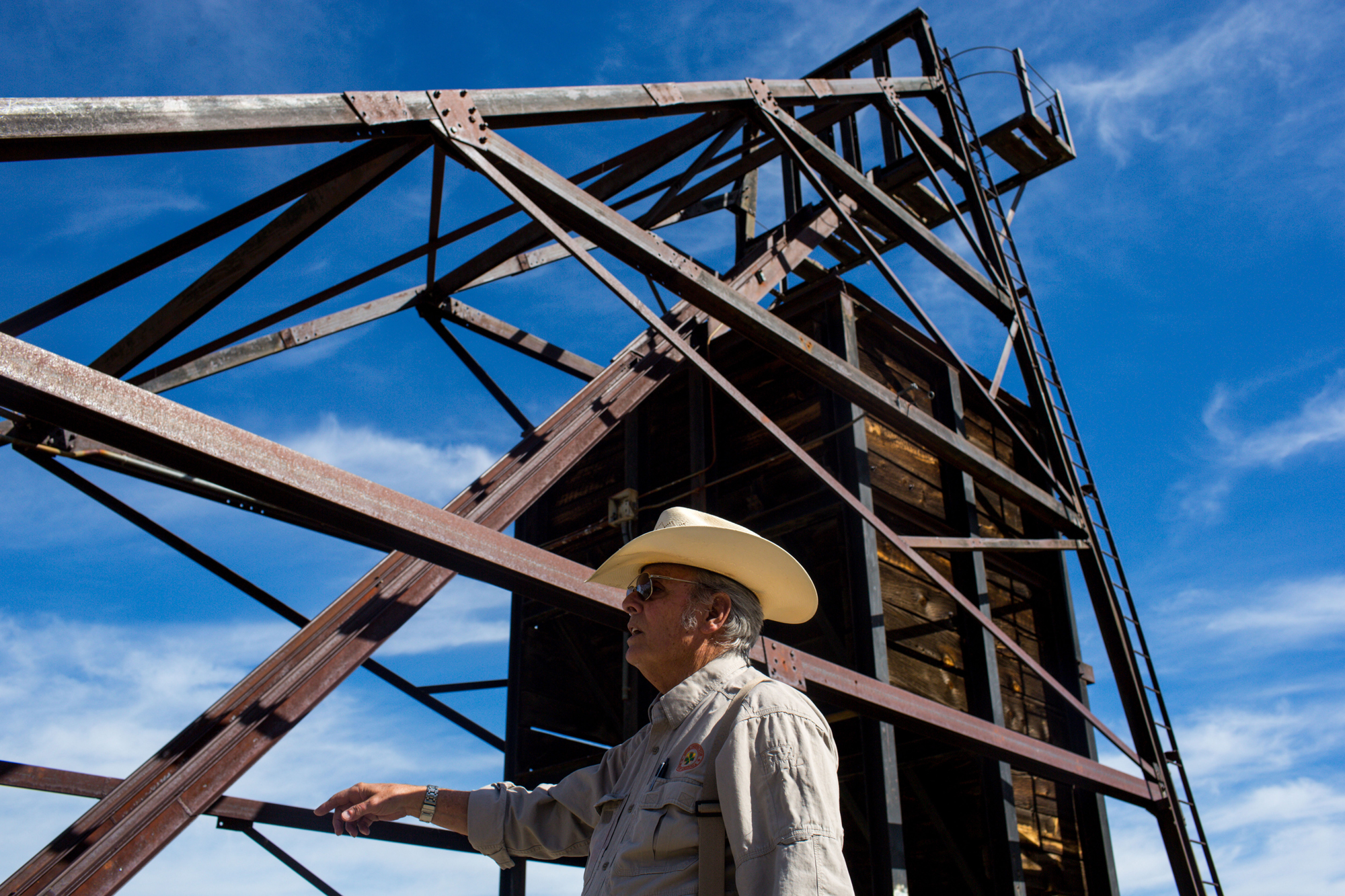 Jerry Tyra, an abandoned mine supervisor, wears a straw cowboy hat as he stands in front of an abandoned mine.