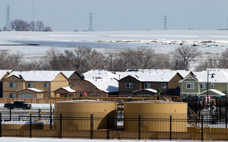 Two oil and gas storage tanks are near homes covered in snow.