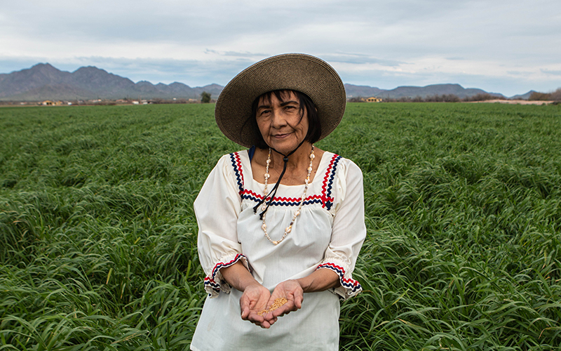 A native woman stands in a field holding seeds as she smiles softly