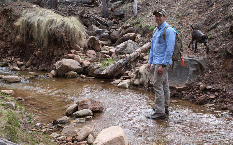 A man standing in a small creek with his dog.