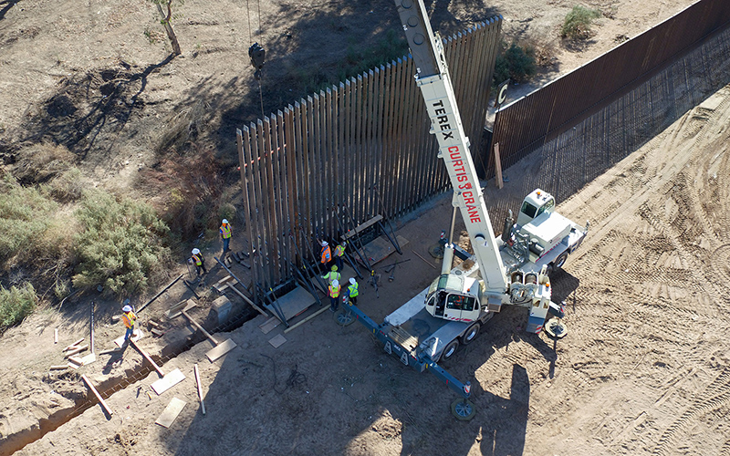 Workers use a crane and additional materials to put up the Yuma wall.