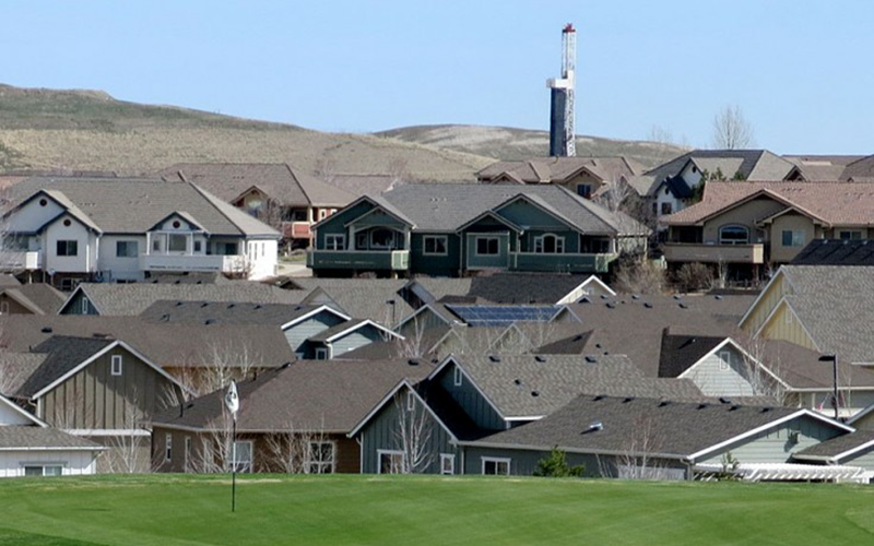 The view from the Colorado National Golf Club includes housing developments and a drilling rig in Erie, Colorado.