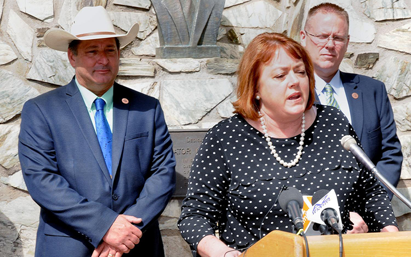 A woman is speaking at a podium while two men stand behind her.