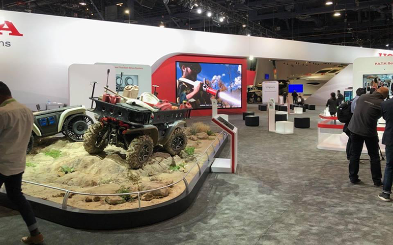 An ATV displayed in a museum with people observing.
