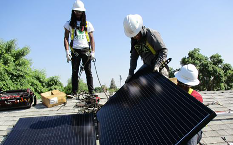Three workers install a set of solar panels on the roof of a home