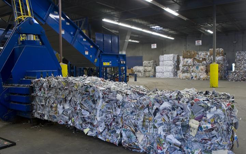 Several large blocks of recycled paper in a warehouse.