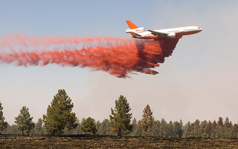 Plane dropping chemical retardant to help fight wildfire.
