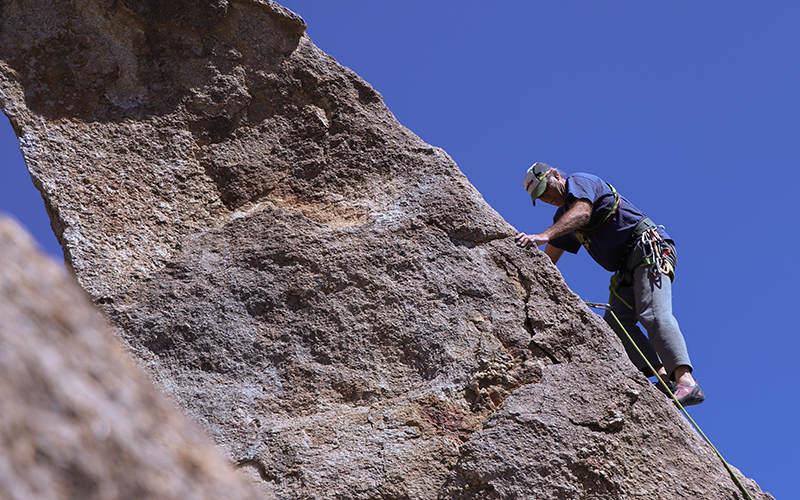 Todd Gordnon climbs a rock formation with assistance from ropes
