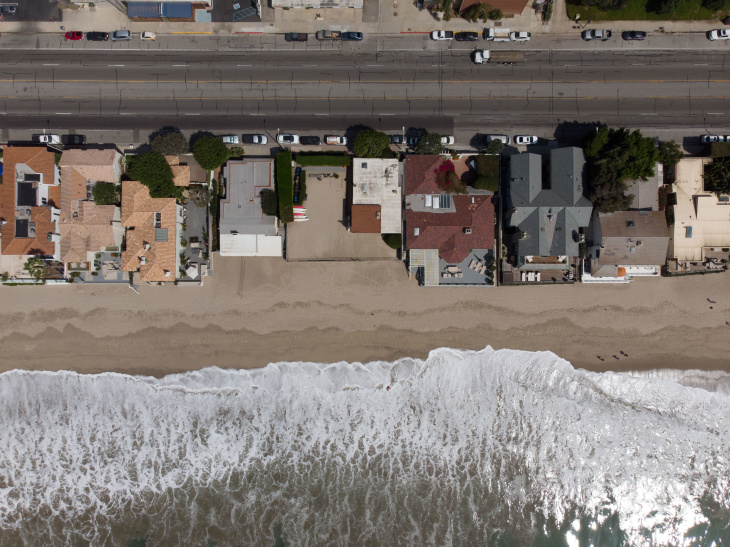 Waves roll onto the beach near ocean front homes