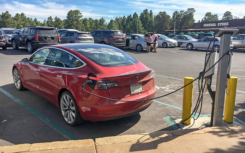 An electric Tesla vehicle recharges in a general store parking lot